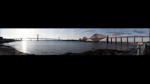 A panoramic view of the Forth Bridges viewed from the south bank of the Firth of Forth. The older rail bridge is to the right, east of the newer road bridge