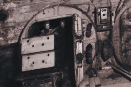 Men moving tunnel lining on railcar through a bulkhead.